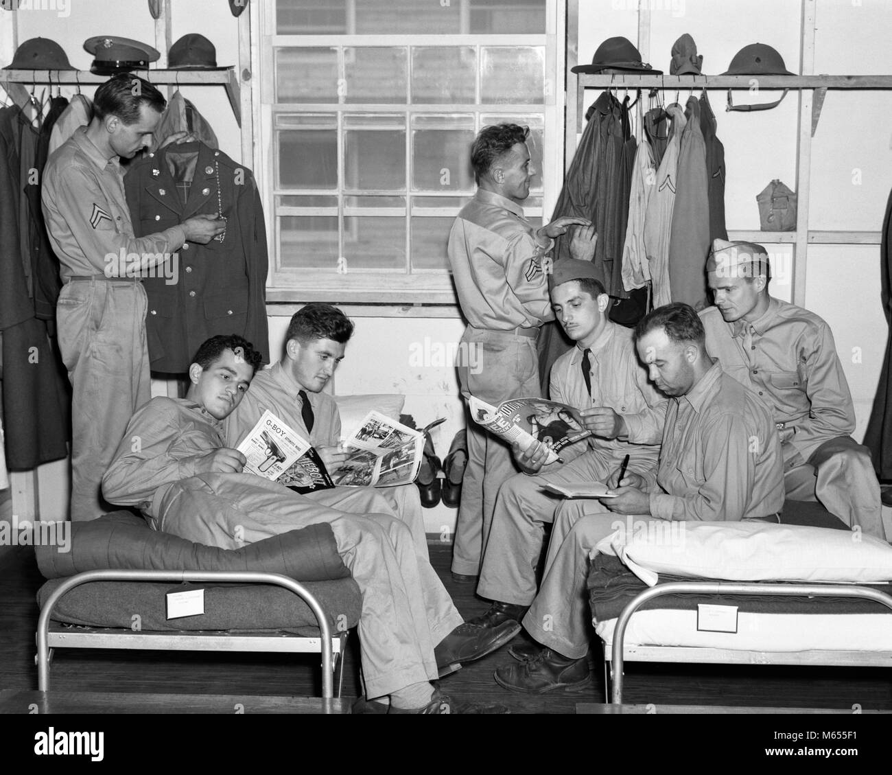 1940s AMERICAN SOLDIERS RELAXING IN BARRACKS READING MAGAZINES AND COMIC BOOKS - a5636 HAR001 HARS TROOPS UNIFORMS - Stock Image
