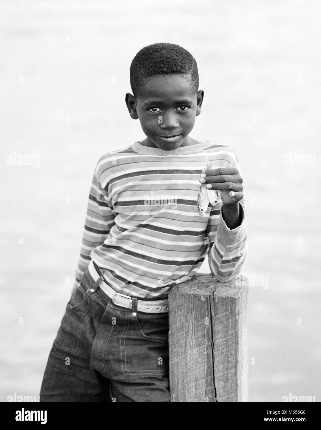 1970s BAHAMIAN BOY IN STRIPED SHIRT WITH SAD FACIAL EXPRESSION LOOKING AT CAMERA ON DOCK HOLDING UP TWO VERY SMALL - Stock Image