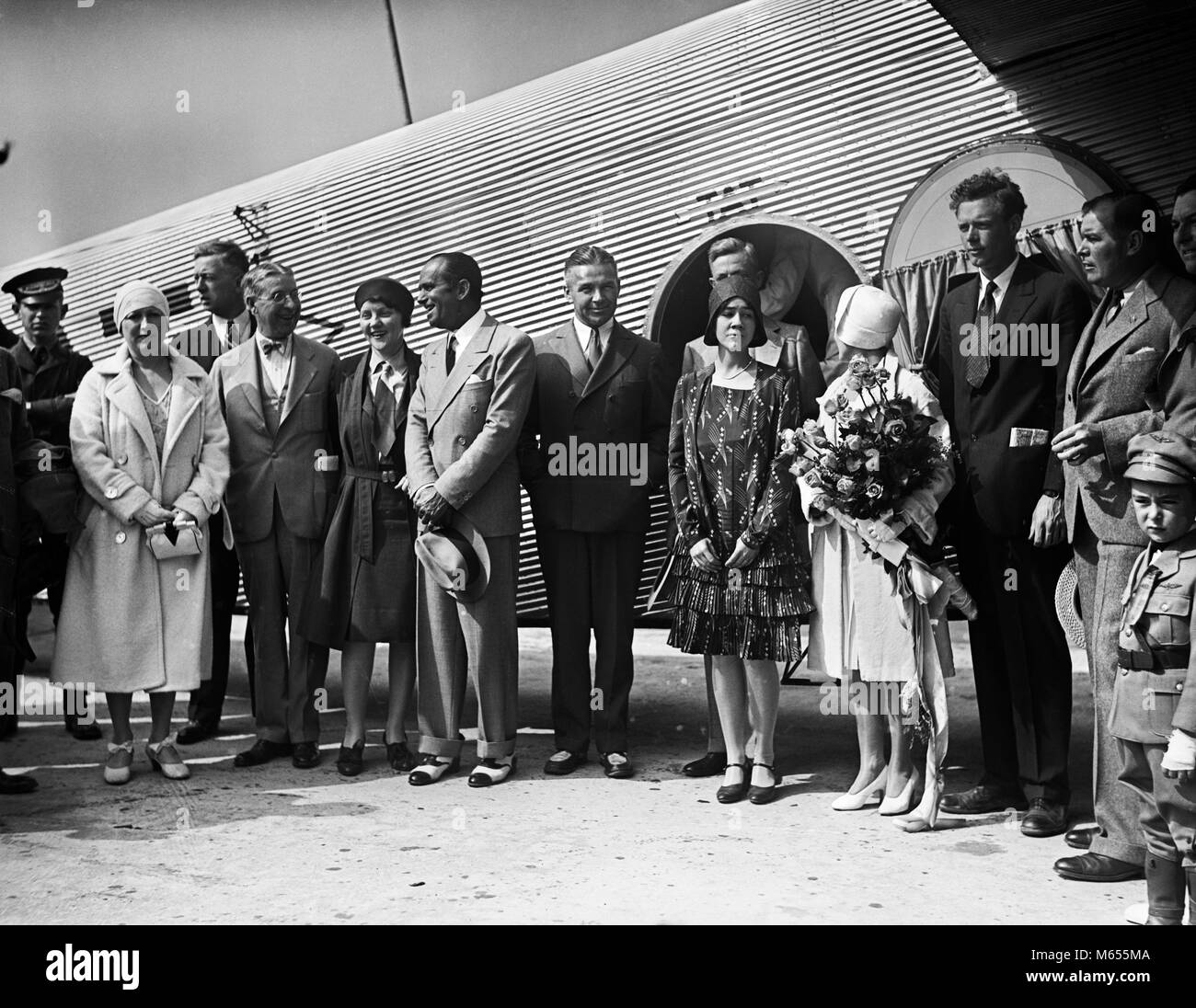 JULY 7 1929 AVIATOR CHARLES LINDBERGH AND WIFE ANNE STANDING BY AIRPLANE WITH GROUP OF PEOPLE - asp_gp90 ASP001 - Stock Image