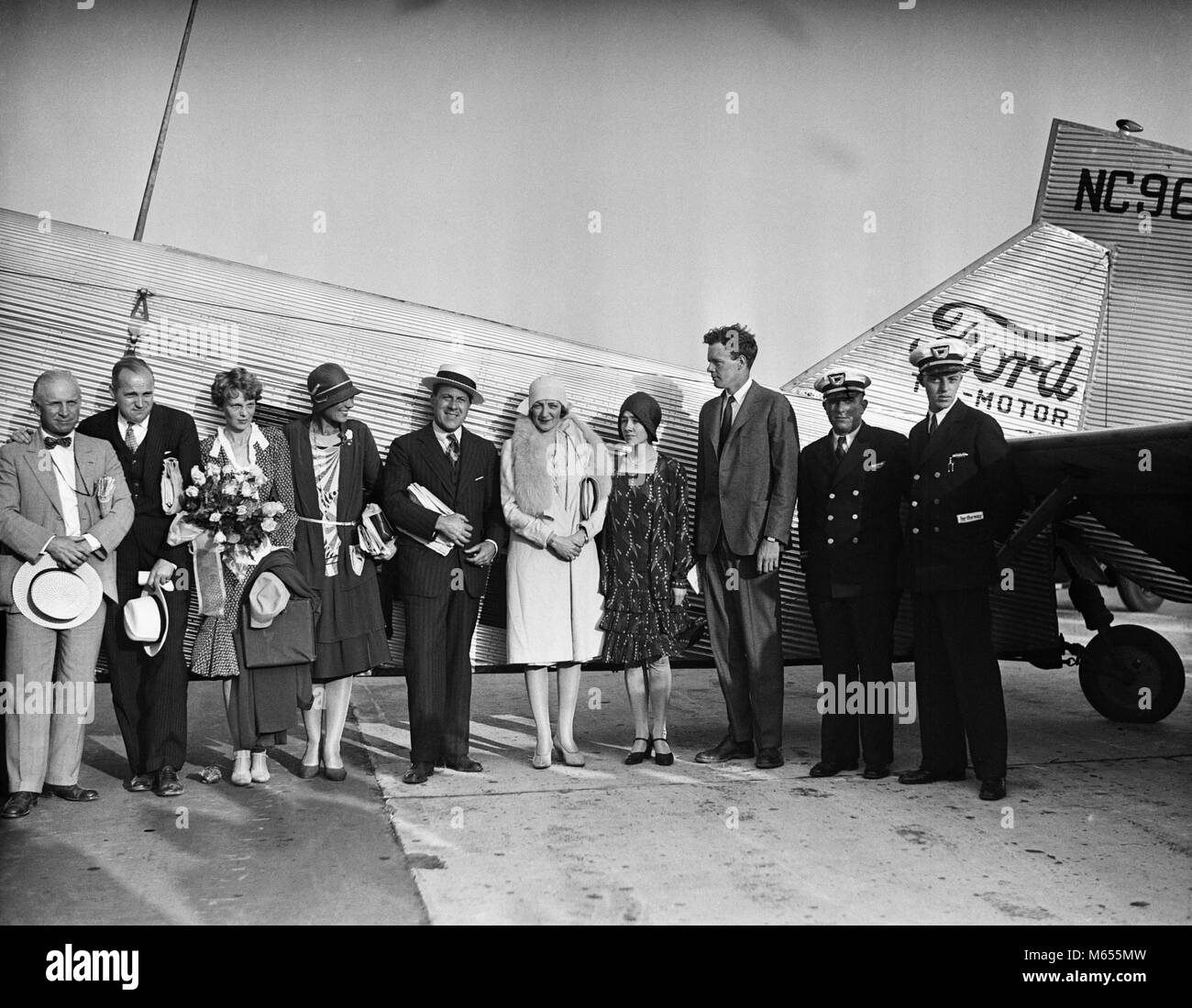 1920s AVIATRIX AMELIA EARHART & AVIATOR CHARLES LINDBERGH & WIFE ANNE STANDING BY FORD TRI-MOTOR AIRPLANE - Stock Image