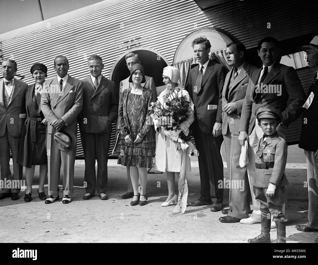 1920s AVIATOR CHARLES LINDBERGH AND HIS WIFE ANNE STANDING BY AIRPLANE WITH GROUP OF PEOPLE ON INAUGURAL FLIGHT - Stock Image