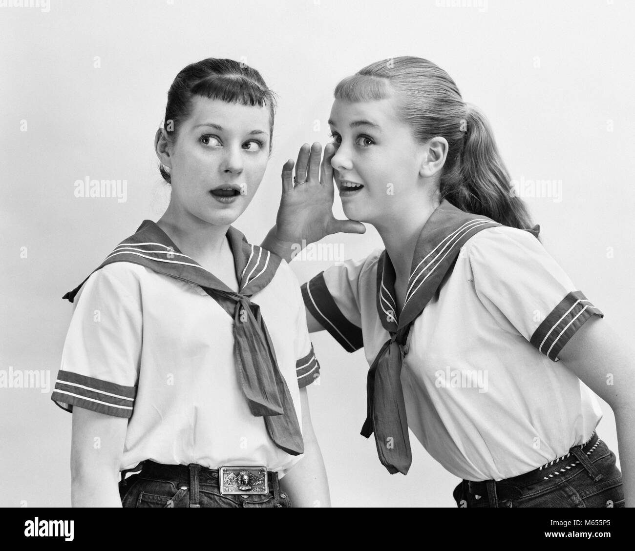 1950s TWO TEENAGED GIRLS WEARING MATCHING NAUTICAL OUTFITS WHISPERING GOSSIPING - asp_x16676 CAM001 HARS PLEASED - Stock Image
