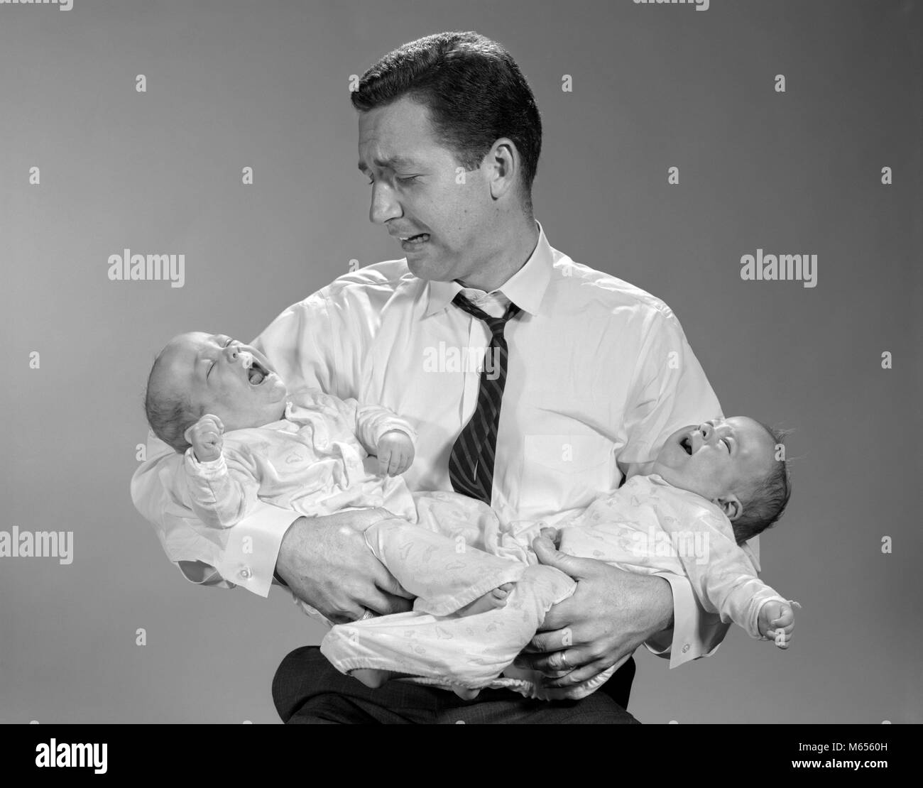 1960s PANICKED MAN FATHER HOLDING CRYING TWIN BABIES - b22022 HAR001 HARS CAUCASIAN SONS DOUBLE LIFESTYLE PARENTING - Stock Image