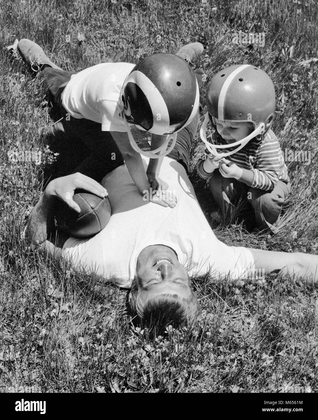 1970s MAN FATHER LYING IN GRASS HOLDING FOOTBALL AFTER BEING TACKLED BY SON AND DAUGHTER - b25063 HAR001 HARS OLD - Stock Image