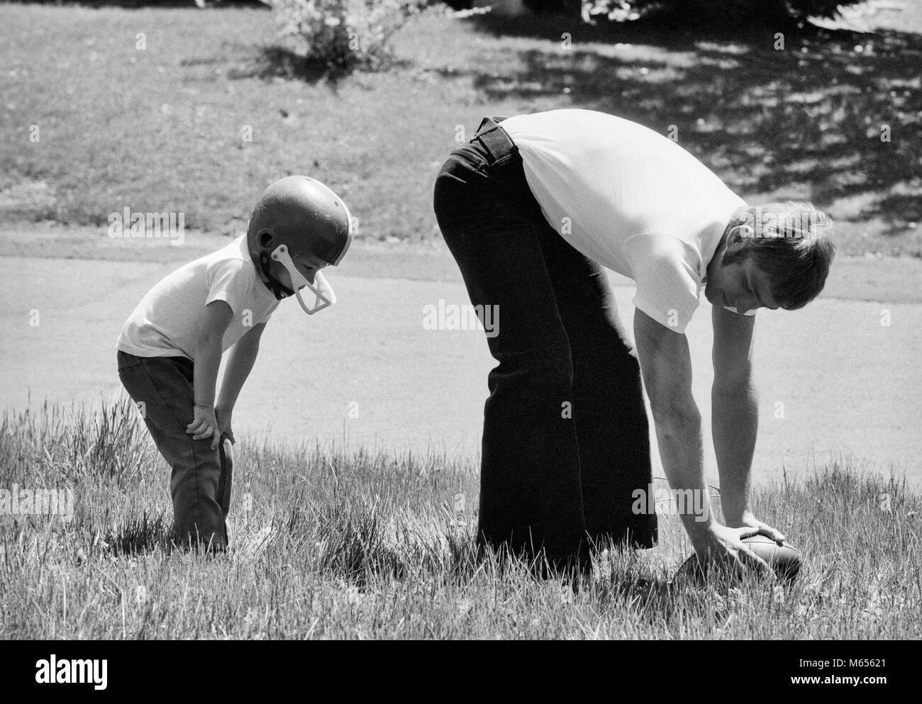 1970s FATHER PLAYING FOOTBALL ON GRASS IN WITH YOUNG SON - b25064 HAR001 HARS JUVENILE YARD BALANCE CENTER TEAMWORK - Stock Image