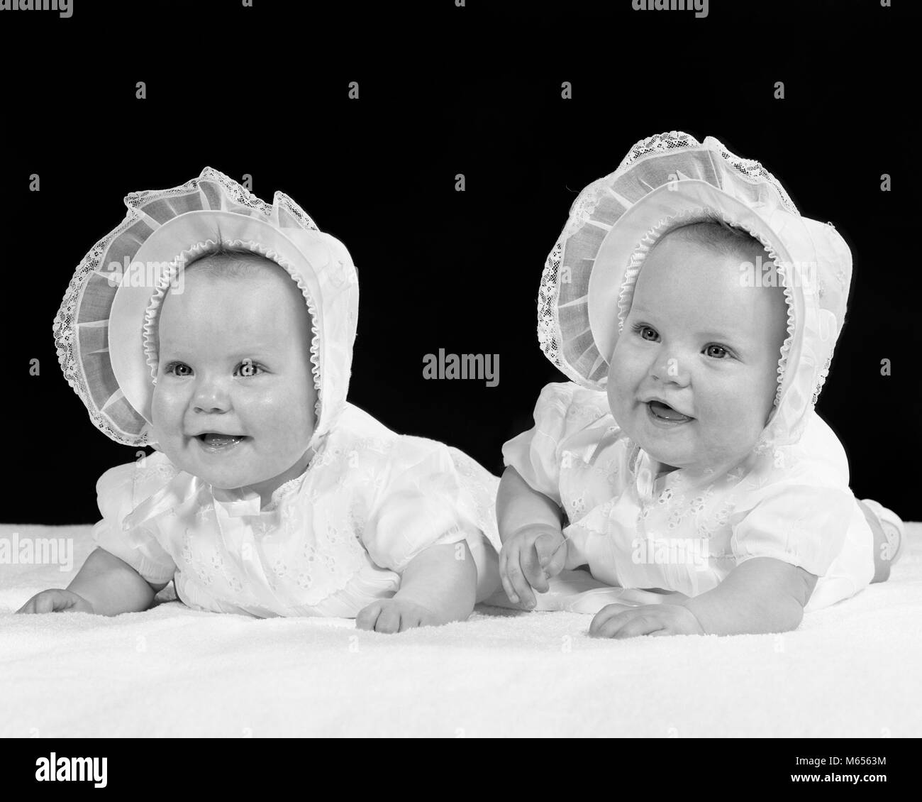 1950s TWIN BABY GIRLS WEARING BONNETS LYING ON THEIR STOMACHS SMILING -  b4985 HAR001 HARS SIBLINGS CHUBBY SISTERS NOSTALGIA TOGETHERNESS 0-1 YEARS  MATCHING ... 29670fe1539