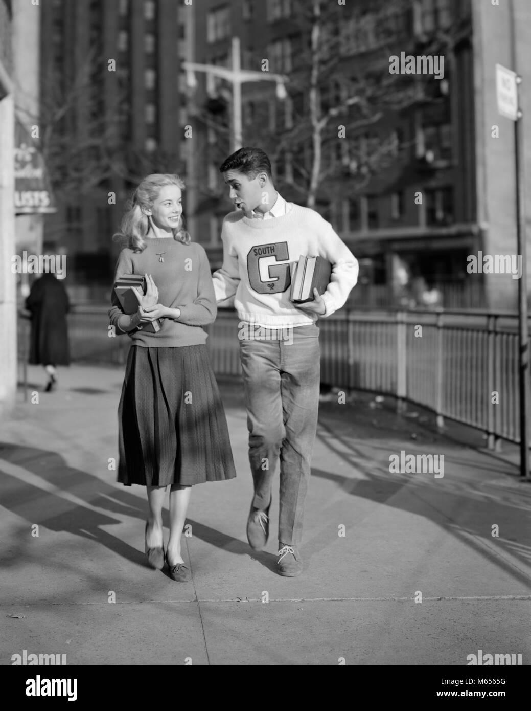 1950s Teenage Boy Wearing Varsity Letter Sweater Walking Girl Home