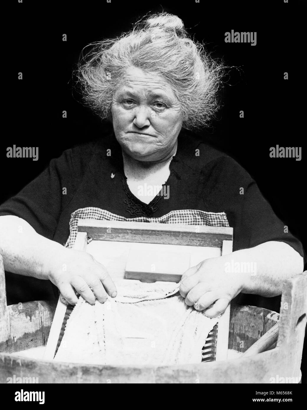 1930s DEPRESSION ERA SENIOR WOMAN SAD FACIAL EXPRESSION WASHING CLOTHES LAUNDRY ON SCRUBBING WASHBOARD LOOKING AT - Stock Image
