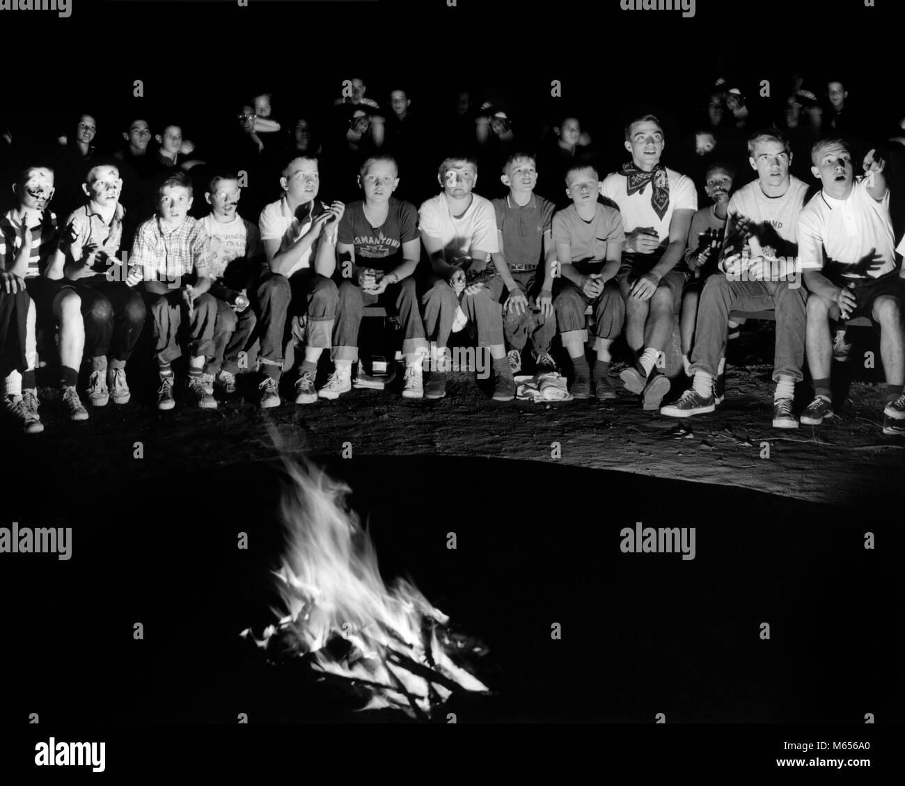 1960s GROUP PRE-TEEN BOYS SITTING AROUND NIGHT CAMPFIRE AT SUMMER CAMP - c9412 HAR001 HARS INSPIRATION AWAY TEENAGE Stock Photo