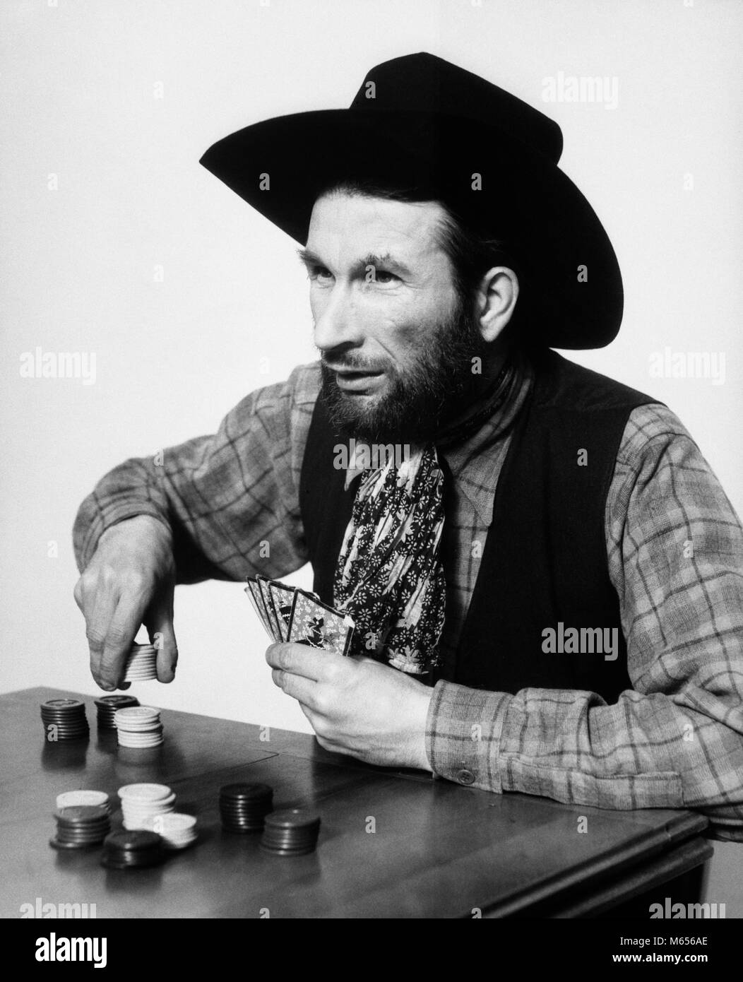 1930s BEARDED MAN COWBOY PLAYING CARDS GAMBLING BETTING POKER CHIPS - c988 HAR001 HARS CHOICE EXCITEMENT LUCKY RECREATION - Stock Image