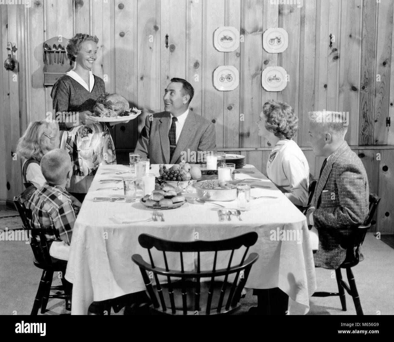 1950s MOTHER SERVING TURKEY ON PLATTER TO SMILING FAMILY AT TABLE IN KNOTTY PINE PANELED DINING ROOM - d4349 HAR001 - Stock Image