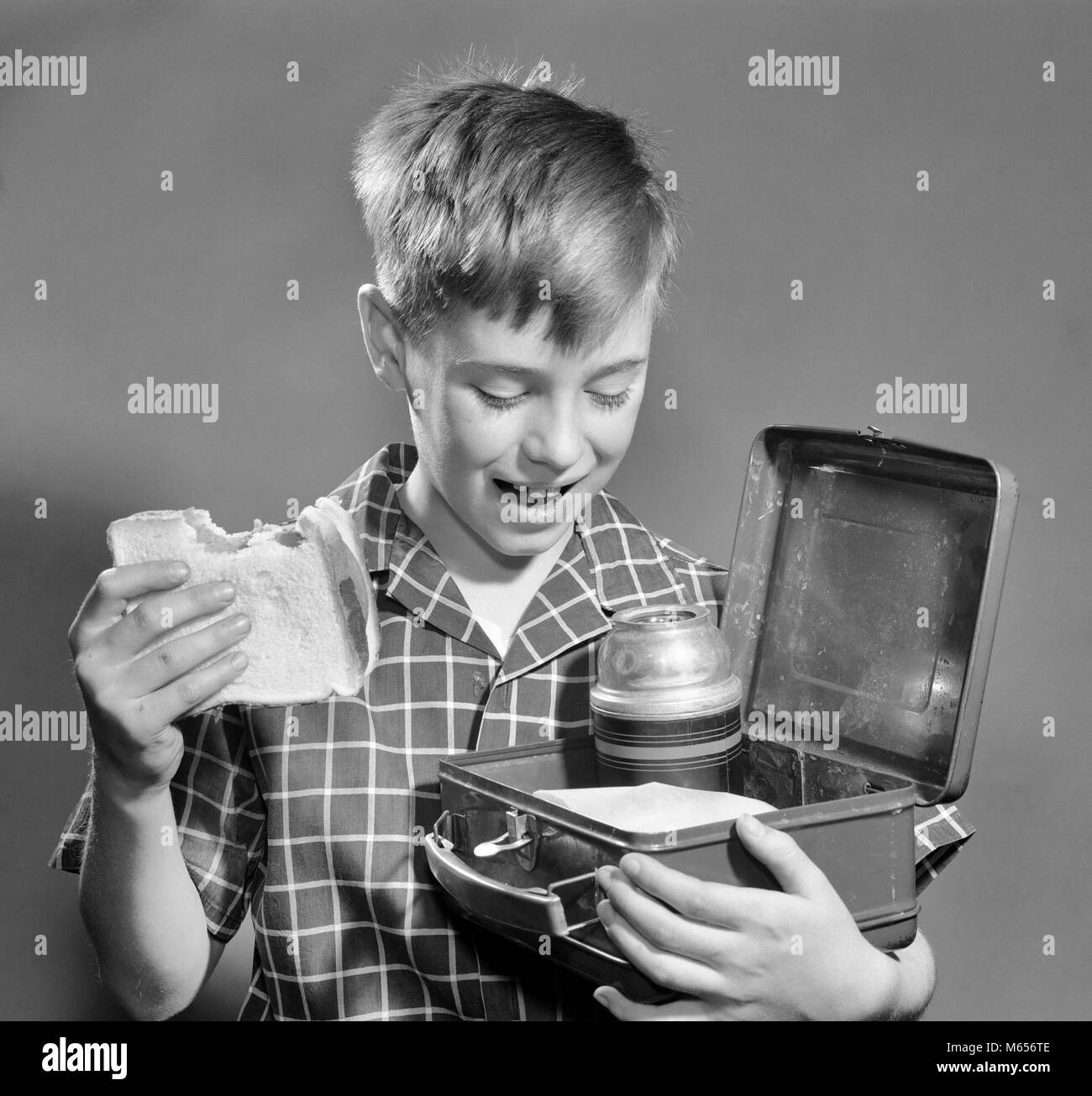 1950s SMILING BOY EATING SANDWICH LOOKING INTO LUNCH BOX WITH THERMOS - f6553 DEB001 HARS COPY SPACE HALF-LENGTH - Stock Image