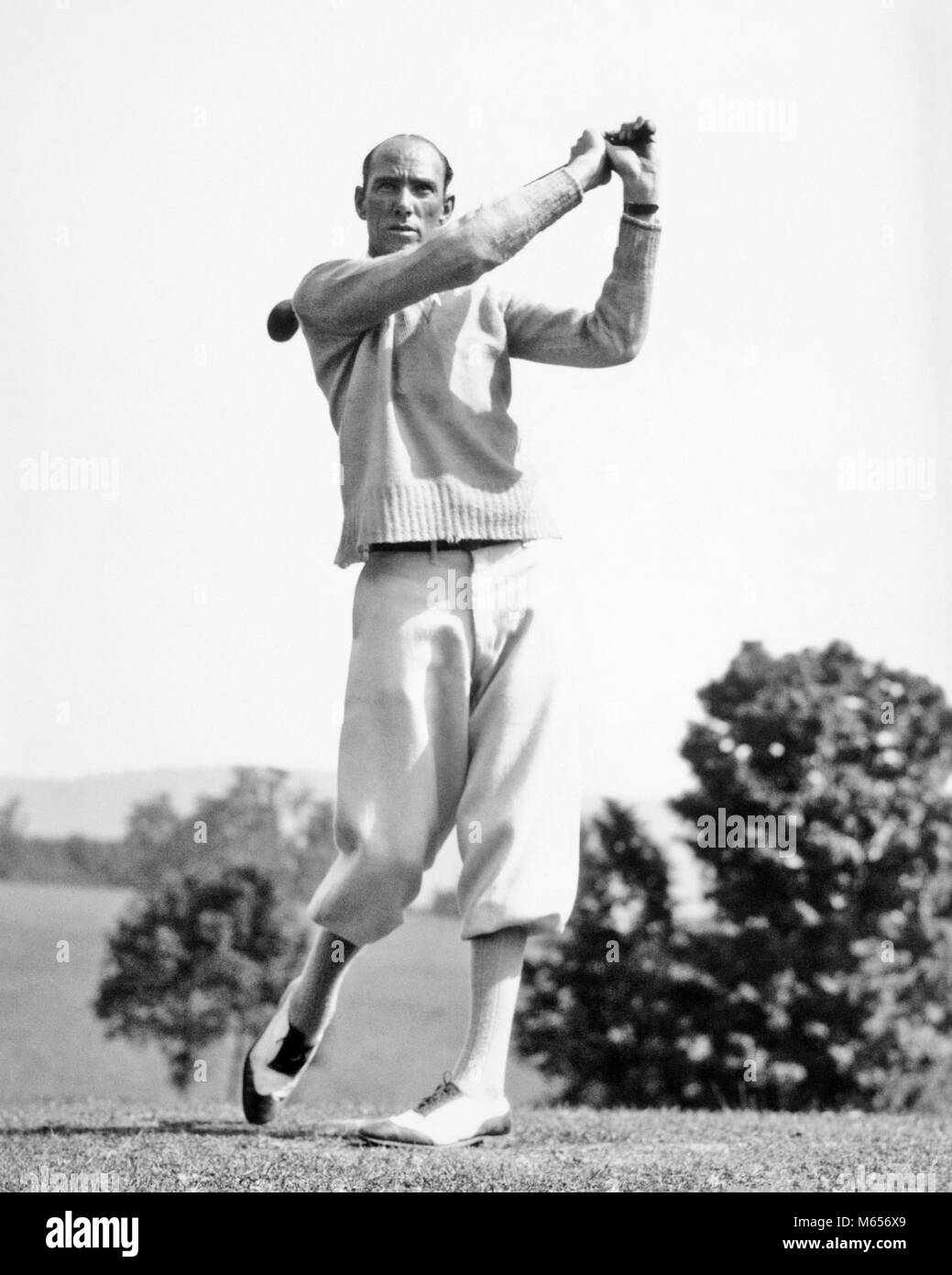 1920s 1930s MAN GOLFER WEARING KNICKERS AND SWEATER SWINGING DRIVER CLUB - g3641 HAR001 HARS HEALTHINESS ONE PERSON - Stock Image