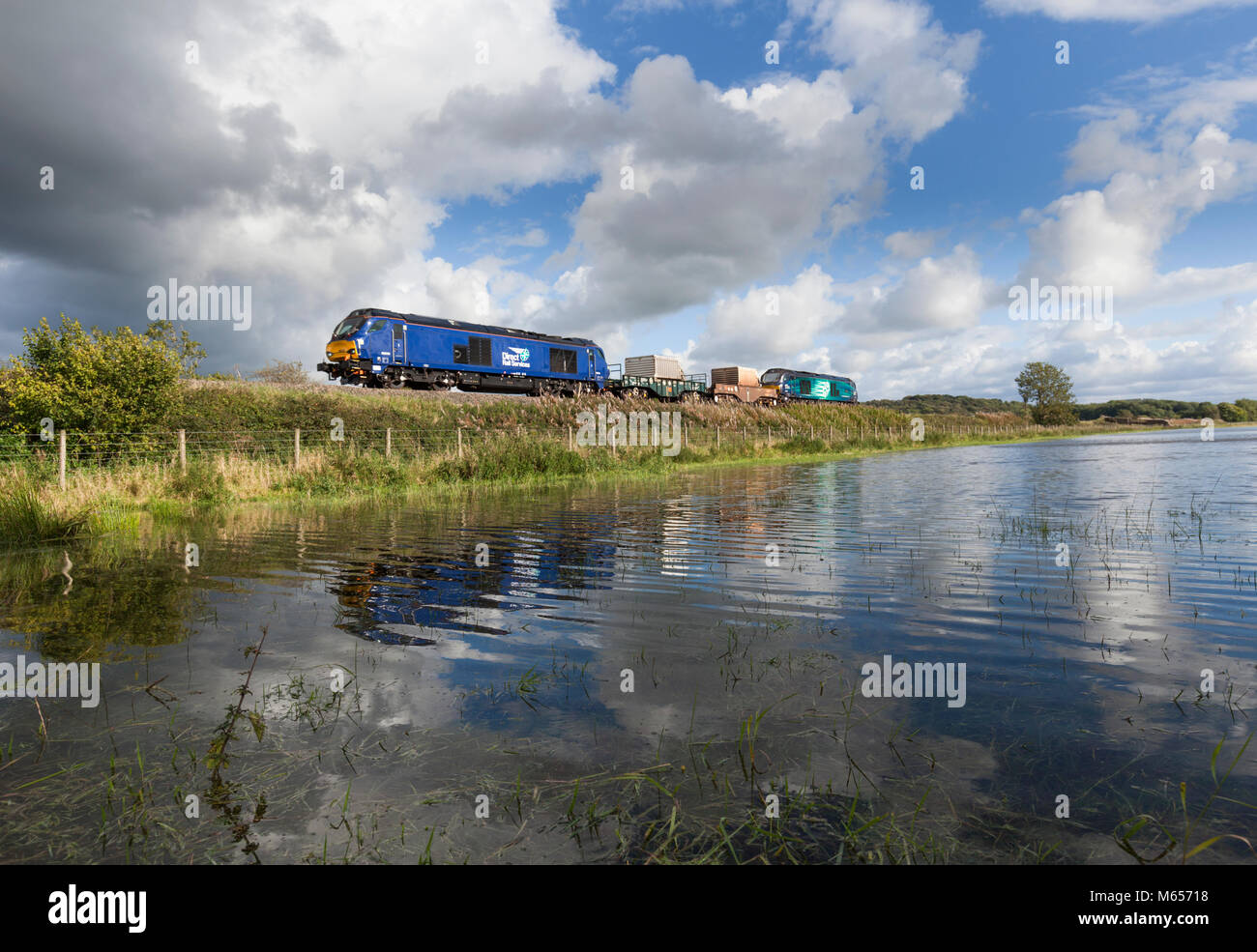 2 Direct rail Services class 68 locomotives reflected in a puddle while working a nuclear flask train from  Heysham - Stock Image