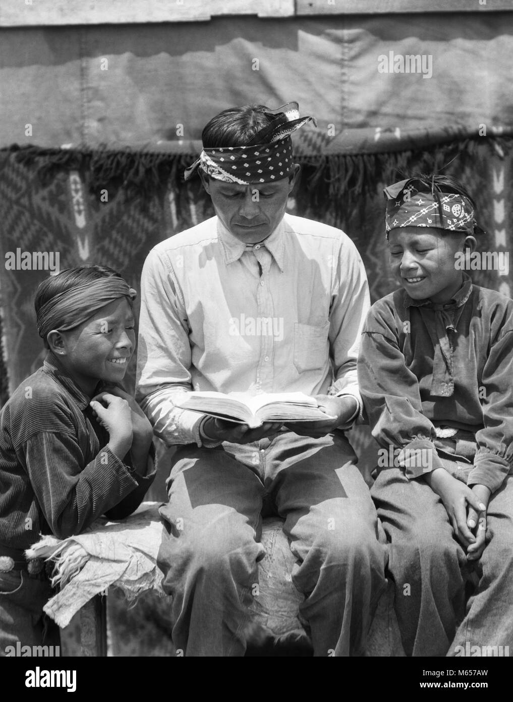 1930s NATIVE AMERICAN INDIAN NAVAJO MAN FATHER READING BOOK TO TWO SMILING BOYS SONS - i1105 HAR001 HARS JUVENILE Stock Photo