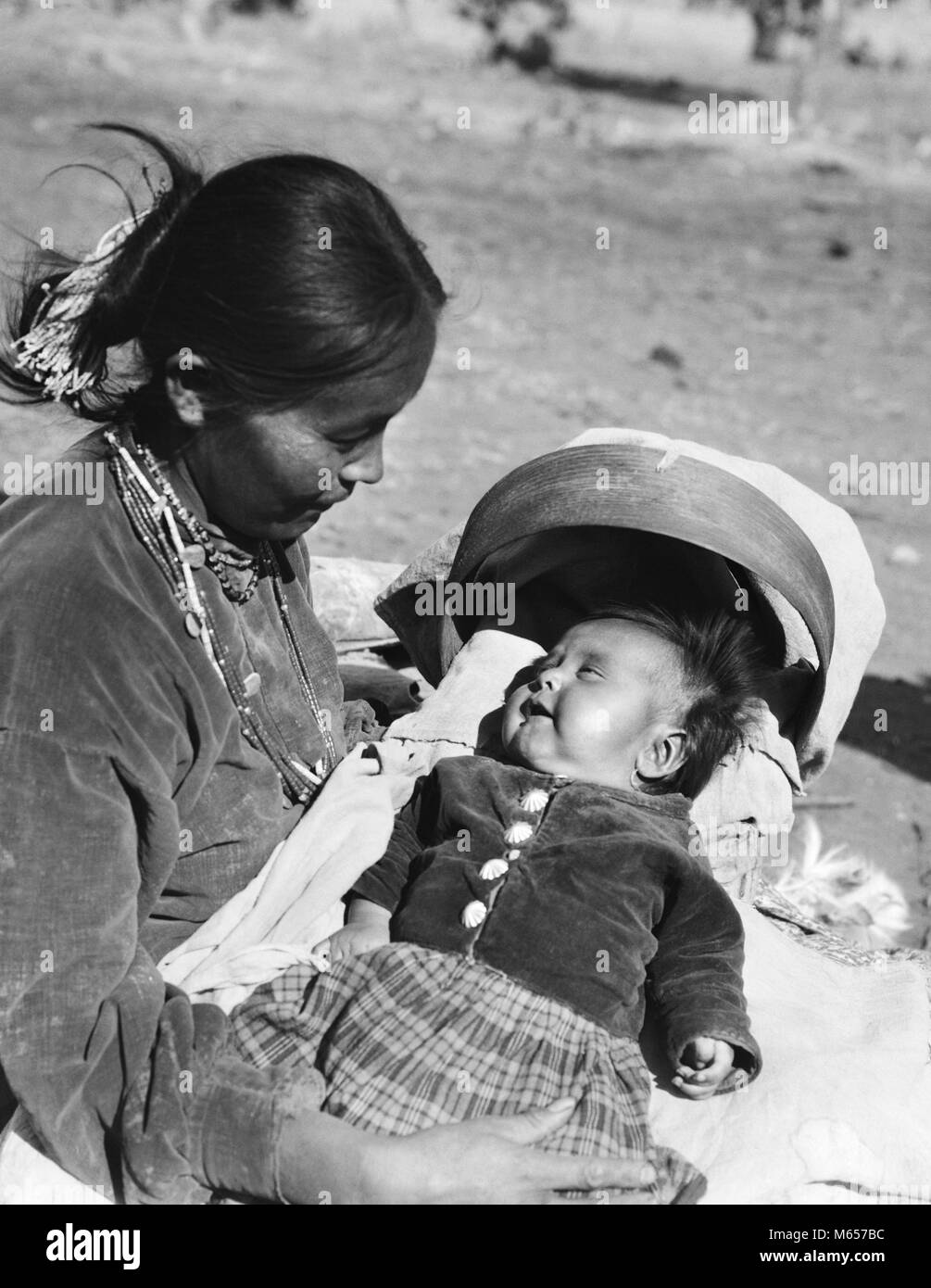 1930s NATIVE AMERICAN NAVAJO INDIAN WOMAN MOTHER HOLDING SMILING BABY PAPOOSE IN CRADLE BOARD - i1125 HAR001 HARS - Stock Image