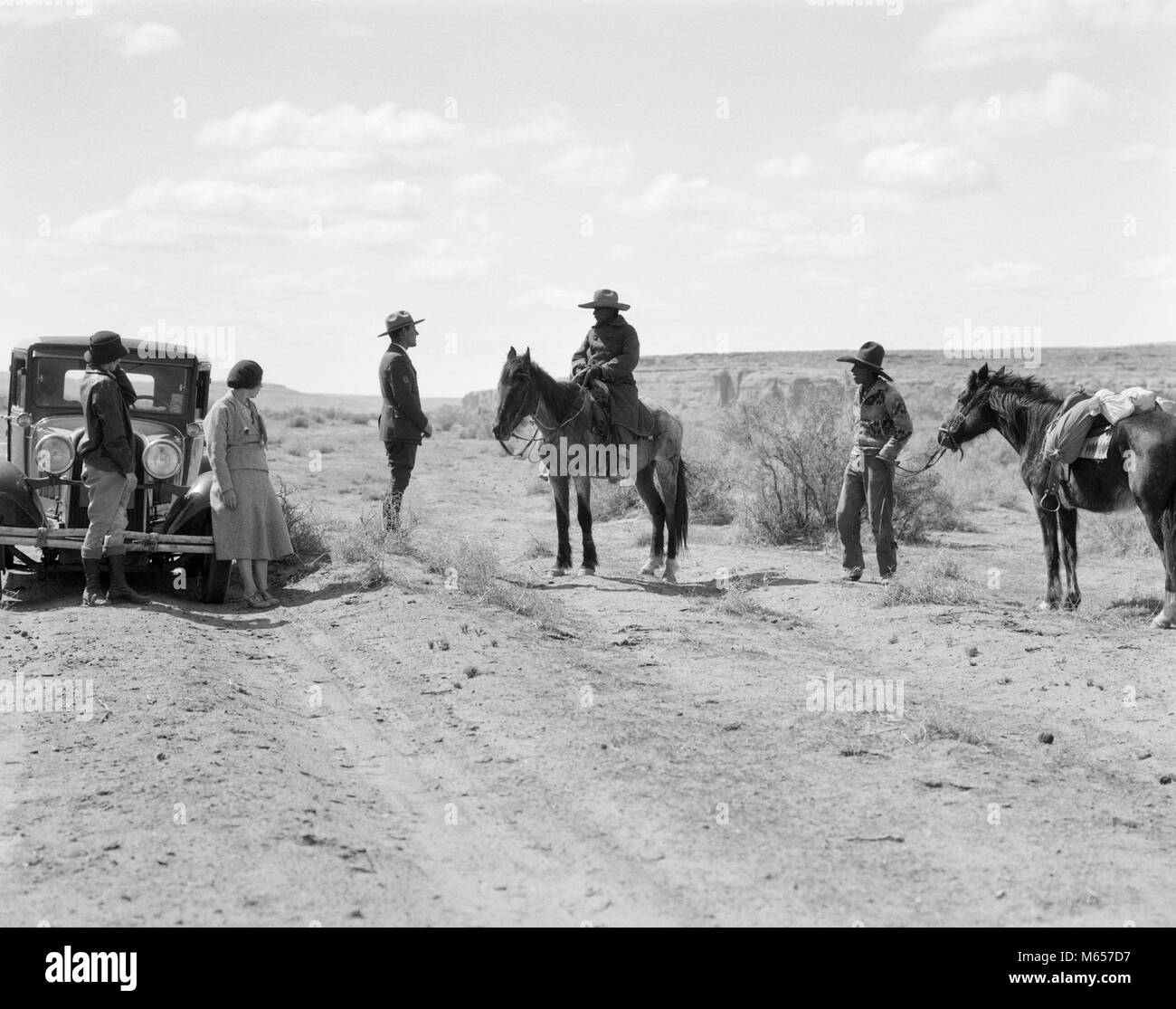 1930s TWO NAVAJO MEN WITH PONIES STOP TO SPEAK TO PARK RANGER WITH TWO WOMEN TOURISTS - i1188 HAR001 HARS AUTOMOBILE - Stock Image
