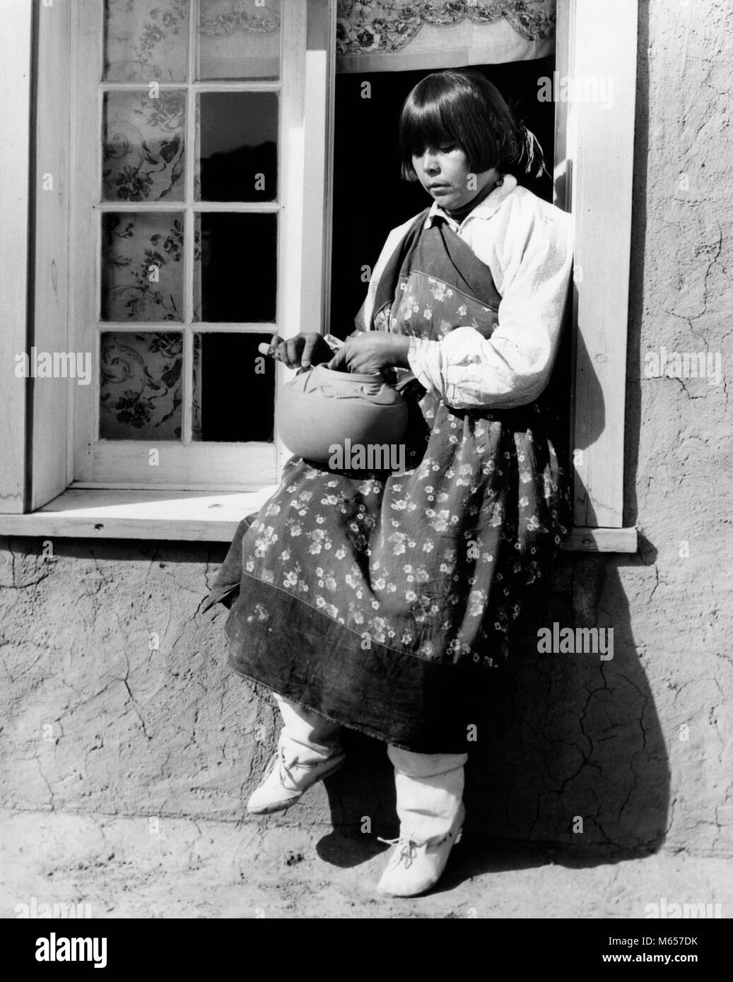 1930s NATIVE AMERICAN WOMAN SITTING ON WINDOWSILL DECORATING POTTERY WEARING TYPICAL COSTUME SAN ILDEFONSO PUEBLO - Stock Image