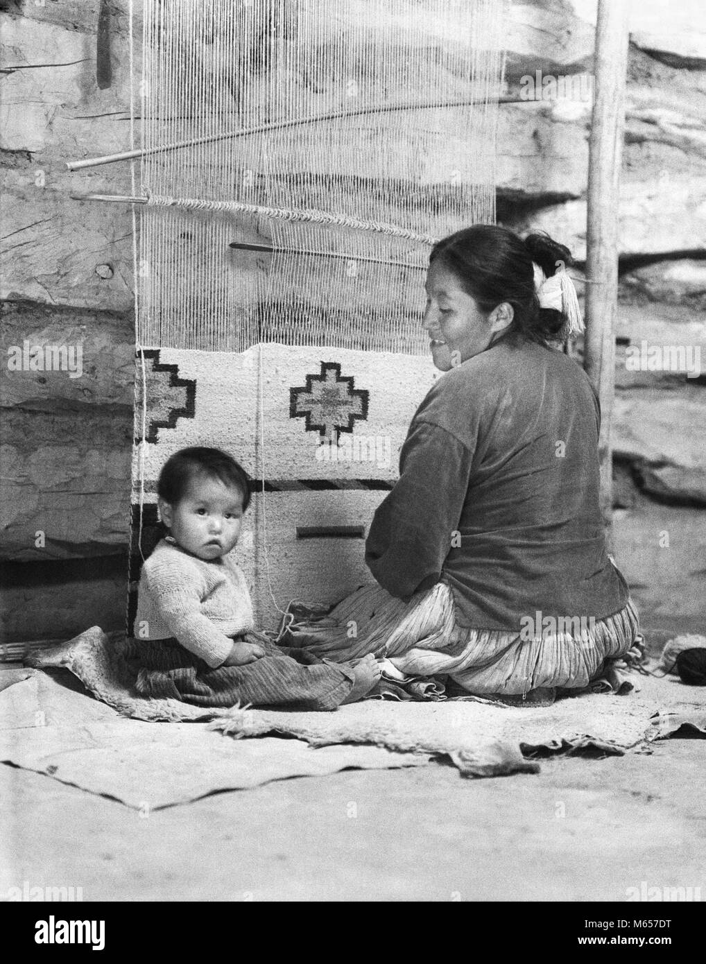 1930s SMILING NATIVE AMERICAN NAVAJO WOMAN MOTHER WEAVING RUG SEATED AT LOOM WITH BABY AT HER SIDE LOOKING AT CAMERA - Stock Image