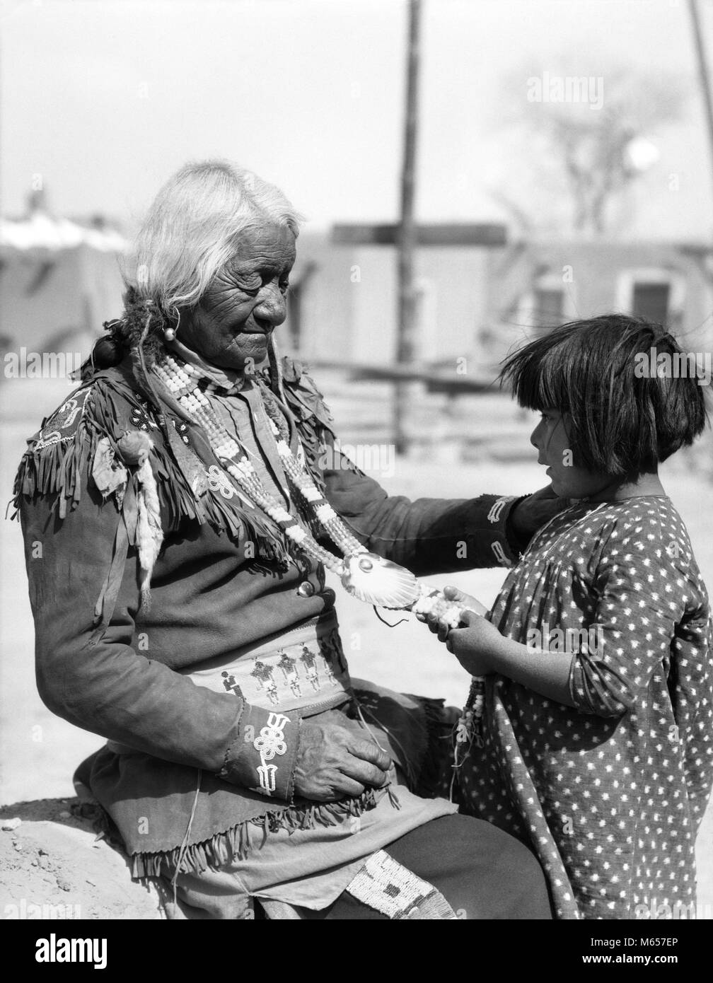 1930s NATIVE AMERICAN CHILD ADMIRING BEADED NECKLACE OF ELDERLY INDIAN MAN SANTA CLARA PUEBLO NEW MEXICO USA - i1344 - Stock Image