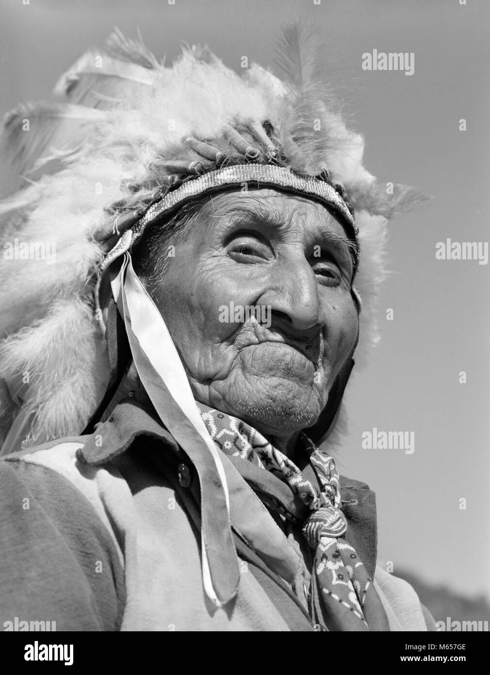1950s 1960s PORTRAIT NATIVE AMERICAN CHEROKEE INDIAN SENIOR MAN WEARING FEATHER HEADDRESS LOOKING AT CAMERA NORTH Stock Photo