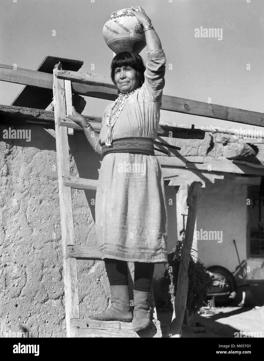 1930s NATIVE AMERICAN INDIAN WOMAN ON LADDER HOLDING OLLA POTTERY JAR ON HER HEAD COCHITI PUEBLO NEW MEXICO USA - Stock Image
