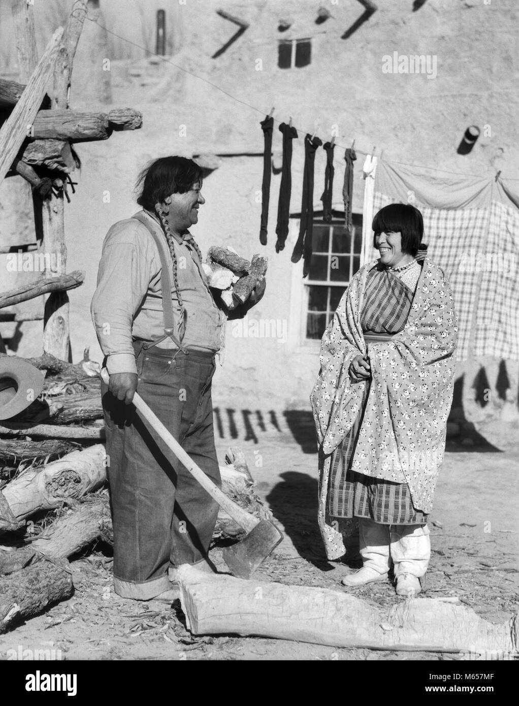 1930s NATIVE AMERICAN COUPLE WOMAN IN TYPICAL COSTUME MAN IN JEANS CHOPPING FIREWOOD WITH AX SAN ILDEFONSO PUEBLO - Stock Image