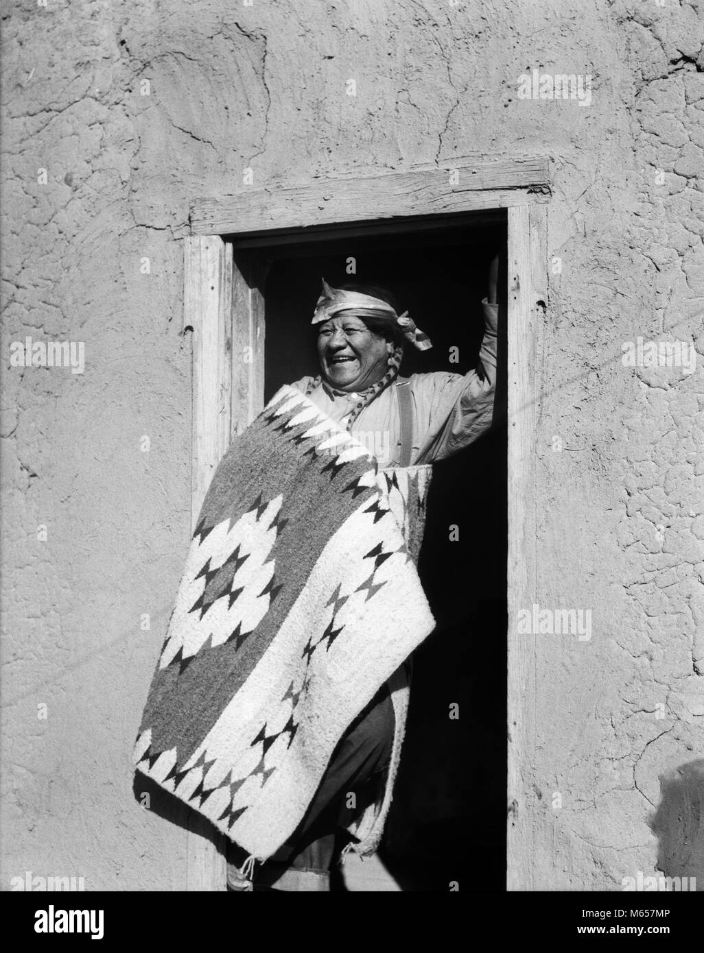 1930s SMILING NATIVE AMERICAN INDIAN MAN STANDING IN DOORWAY WEARING TYPICAL COSTUME SAN ILDEFONSO PUEBLO NEW MEXICO - Stock Image