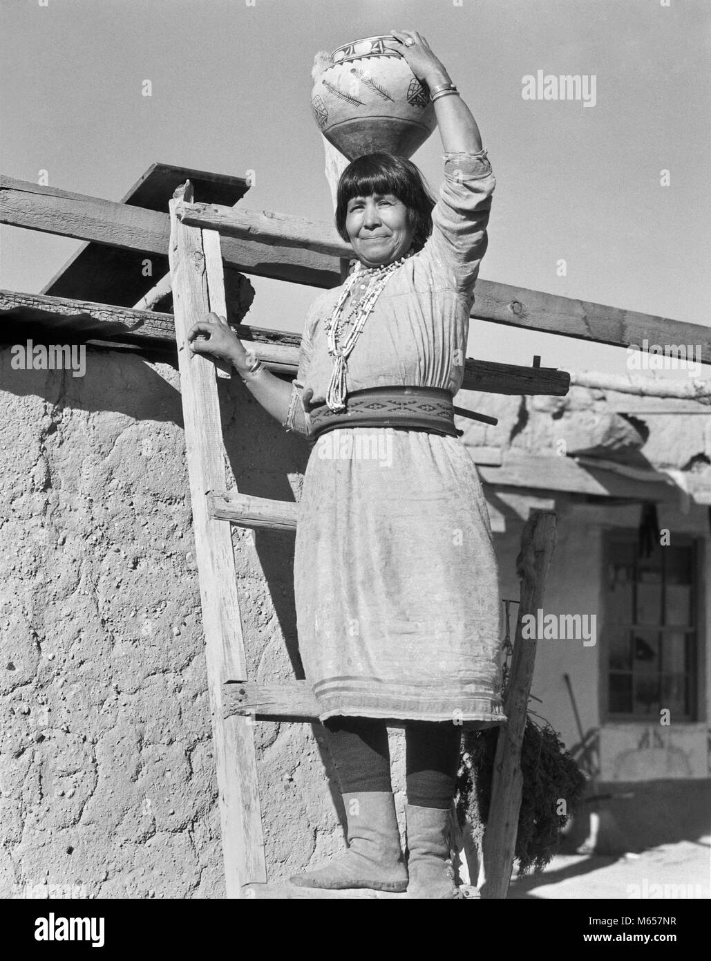 1930s NATIVE AMERICAN INDIAN WOMAN STANDING ON LADDER HOLDING OLLA WATER JAR POTTERY ON HER HEAD COCHITI PUEBLO - Stock Image