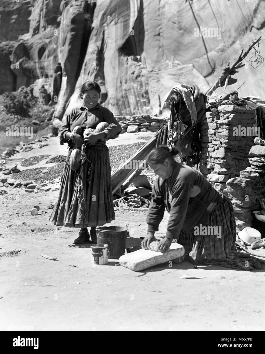 1930s TWO NATIVE AMERICAN NAVAJO INDIAN WOMEN GRINDING CORN AND HARVESTING SQUASH CANYON DEL MUERTO ARIZONA USA - Stock Image