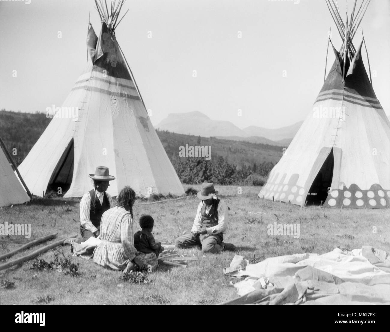 1920s NATIVE AMERICAN INDIAN FAMILY MAN WOMAN TWO CHILDREN SITTING IN FRONT OF TEPEES SIOUX TRIBE MONTANA USA - - Stock Image