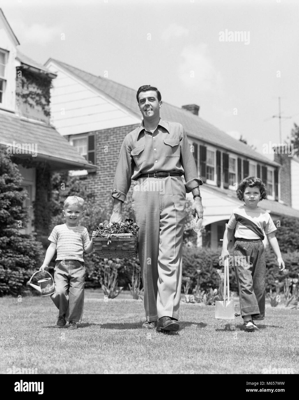 1950s FATHER WITH TWO CHILDREN DAUGHTER AND SON WALKING IN FRONT YARD CARRYING GARDENING TOOLS LOOKING AT CAMERA - Stock Image