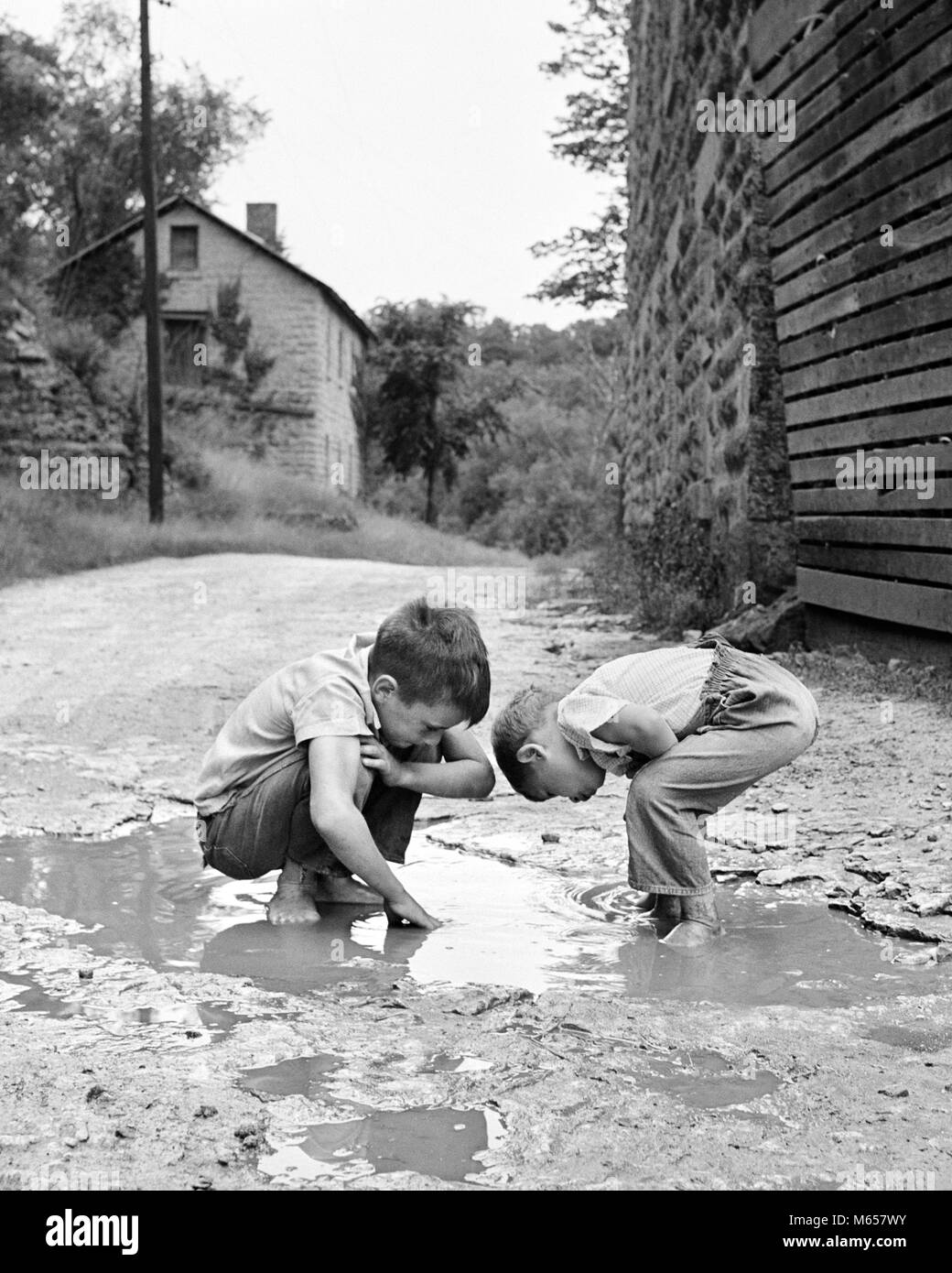 1950s 1960s TWO BOYS BENDING LOOKING AT PLAYING IN MUD PUDDLE - j11747 HAR001 HARS INSPIRATION UNITED STATES OF - Stock Image
