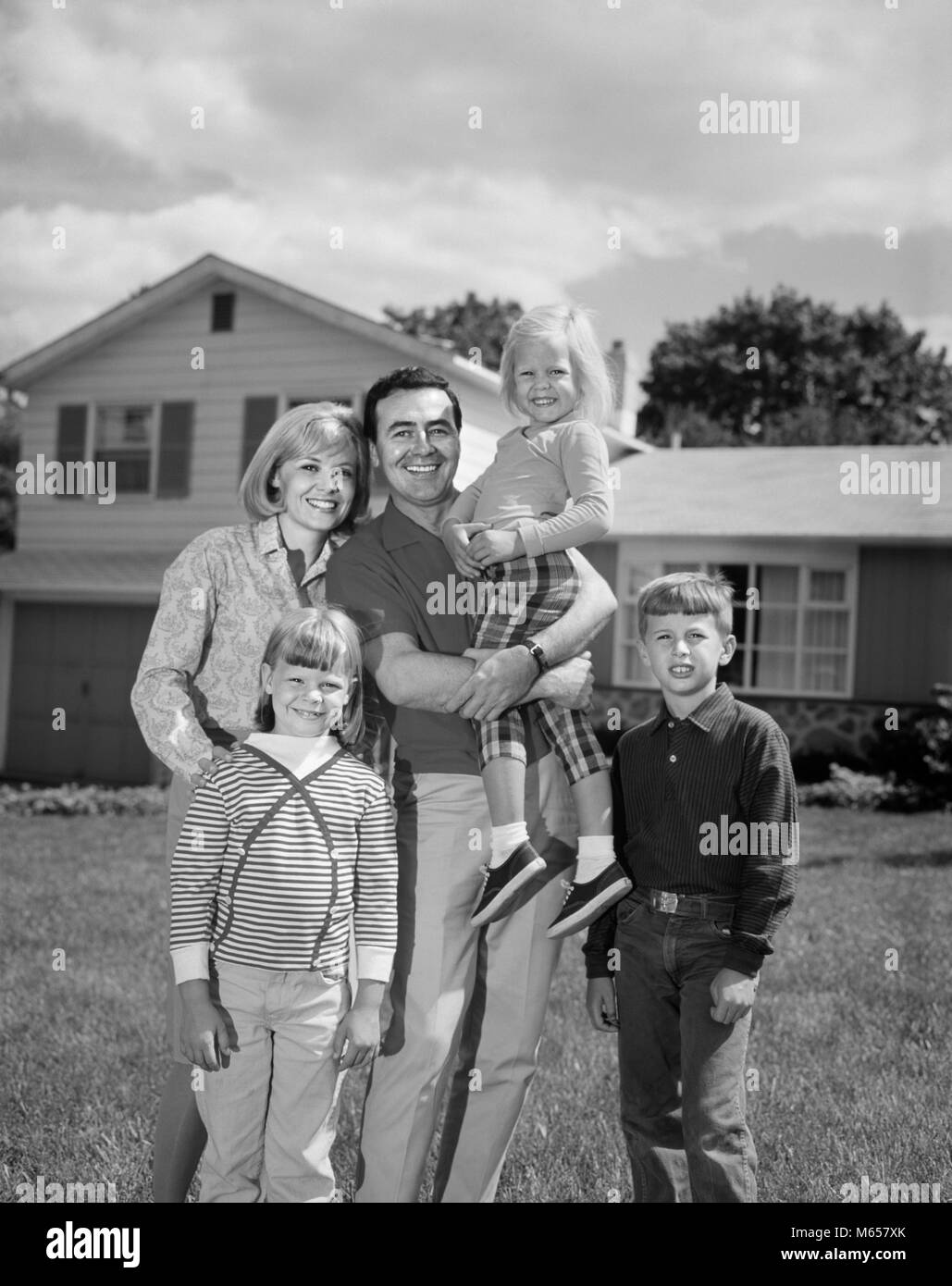 1960s 1970s FAMILY PORTRAIT OF FIVE POSED LOOKING AT CAMERA ON FRONT LAWN OF SUBURBAN HOUSE - j13144 HAR001 HARS - Stock Image