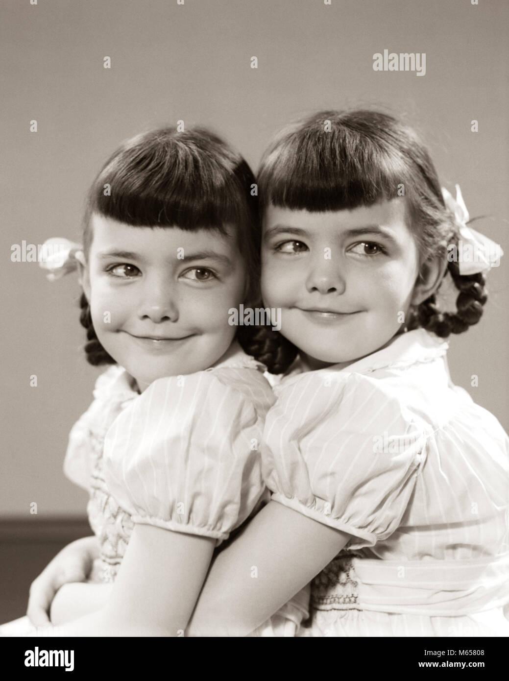 1940s 1950s TWIN GIRLS SMILING HUGGING - j1832 HAR001 HARS SIBLINGS SISTERS NOSTALGIA TOGETHERNESS 3-4 YEARS BRUNETTE - Stock Image