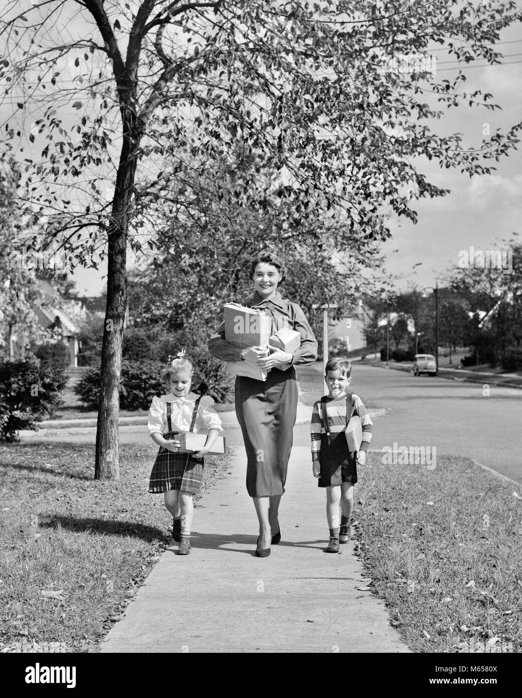 1950s MOTHER TWO CHILDREN WALKING DOWN AUTUMN SUBURBAN SIDEWALK CARRYING SHOPPING PACKAGES LOOKING AT CAMERA - j2439 - Stock Image