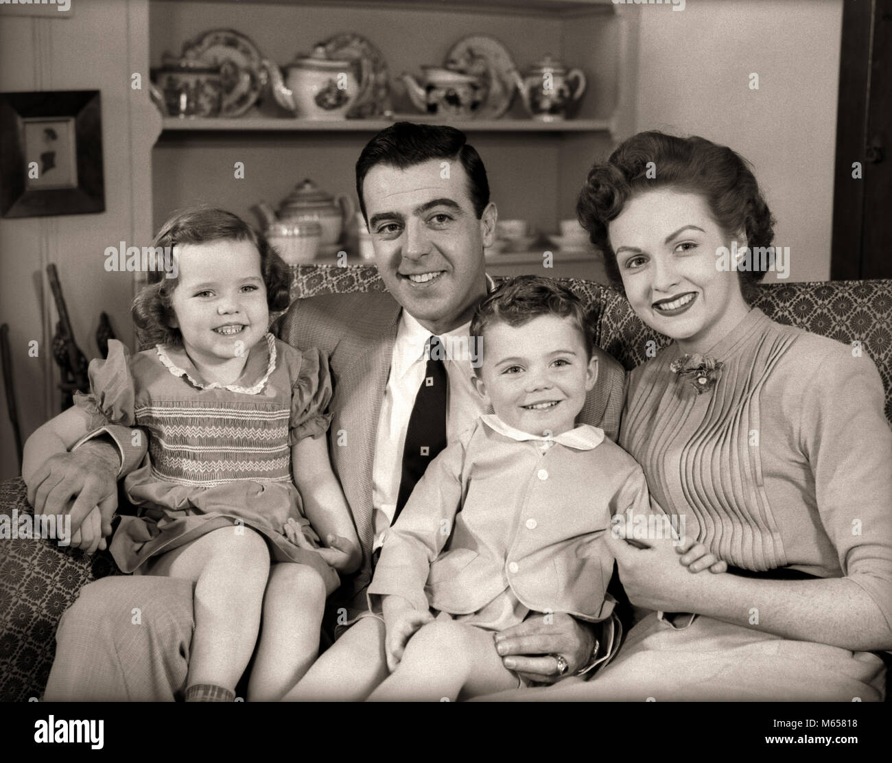1950s FAMILY SITTING ON LIVING ROOM COUCH TOGETHER SMILING LOOKING AT CAMERA - j3908 HAR001 HARS FUTURE BROTHER - Stock Image