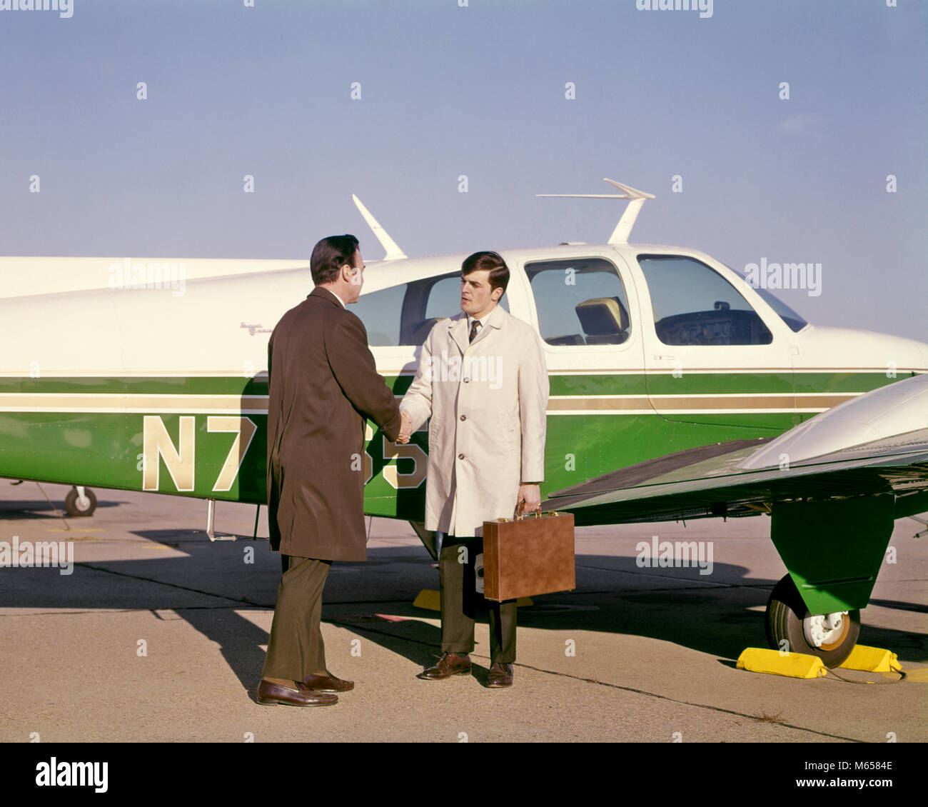 1960s TWO BUSINESS MEN SHAKING HANDS STANDING BESIDE SMALL PRIVATE AIRPLANE - ka1665 HAR001 HARS INFORMATION CAUCASIAN - Stock Image