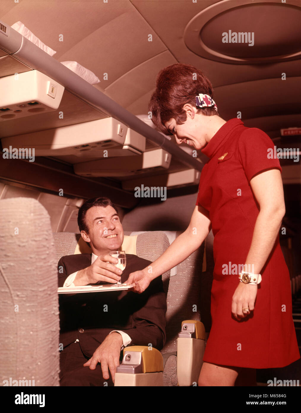 1960s 1970s AIRPLANE PLANE STEWARDESS SERVING BUSINESS MAN DRINK WINE WOMAN COMMERCIAL AIR TRAVEL - ka1667 HAR001 - Stock Image
