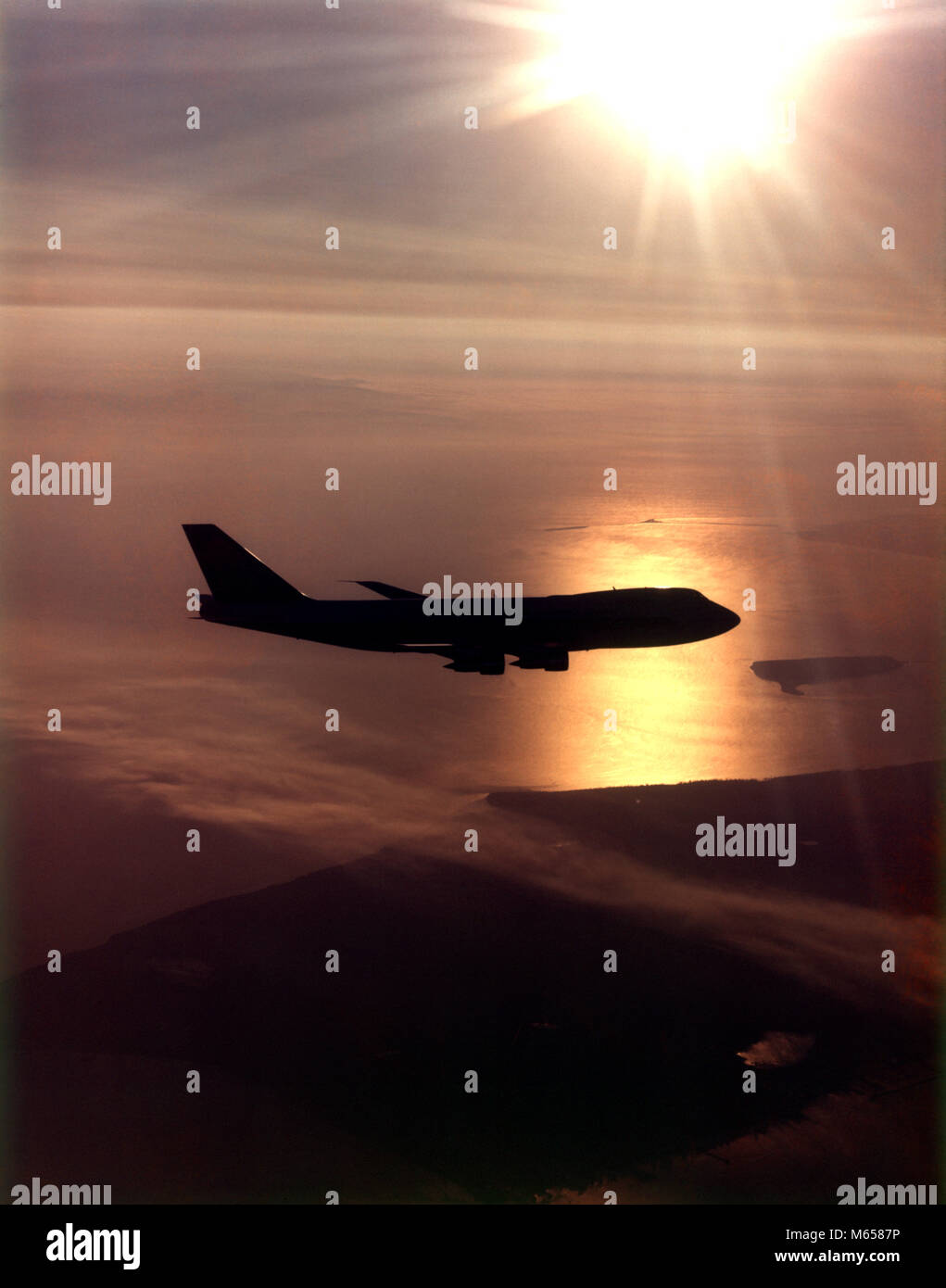 1970s SILHOUETTE BOEING 747 AIRPLANE FLYING IN SUNSET SKY COMMERCIAL AVIATION AIR TRAVEL OVER WATER - ka4346 HAR001 - Stock Image