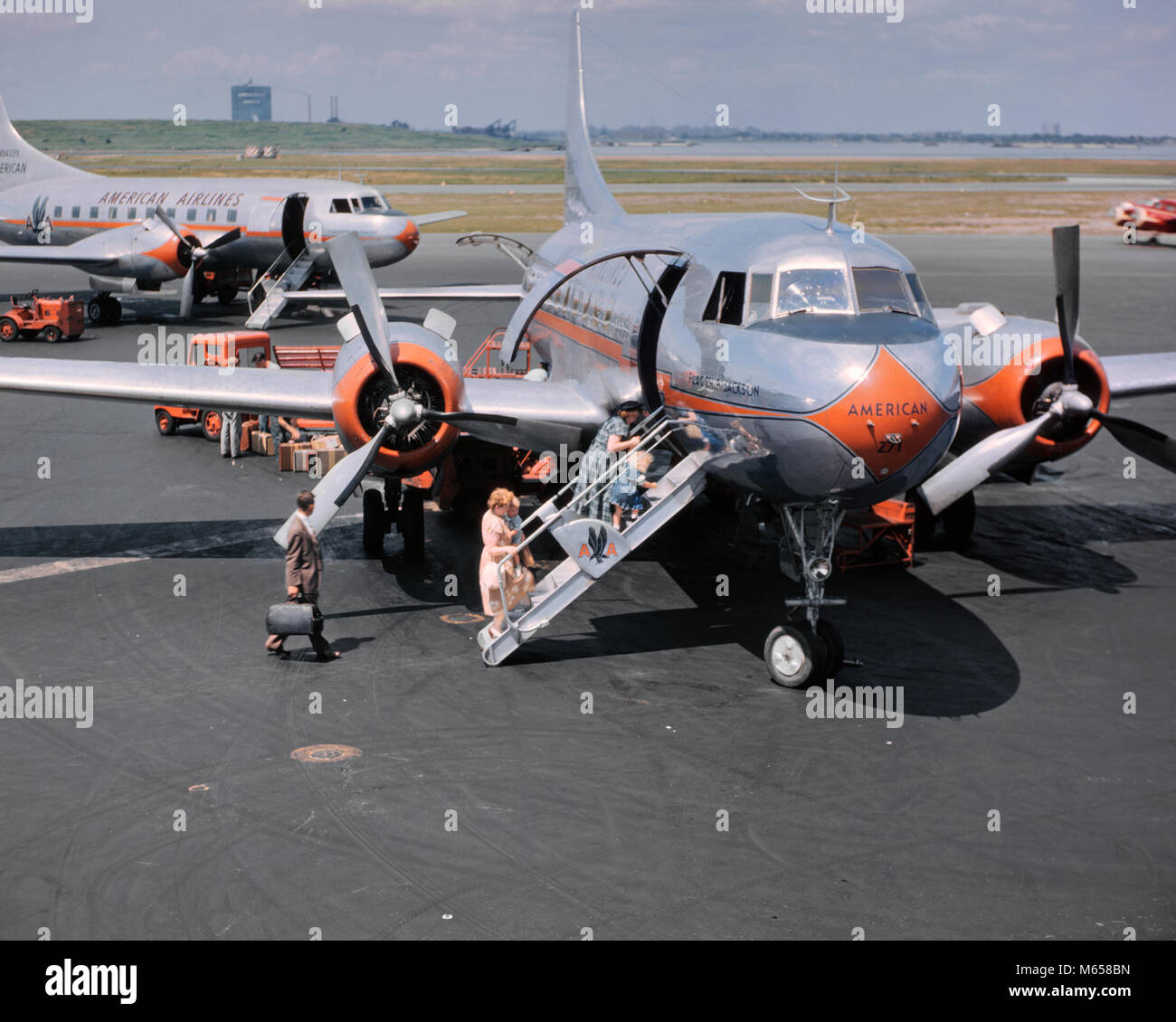 1950s TWO AMERICAN AIRLINE PROPELLER AIRPLANES ON TARMAC WITH PASSENGERS CLIMBING ABOARD LAGUARDIA AIRPORT NEW YORK - Stock Image