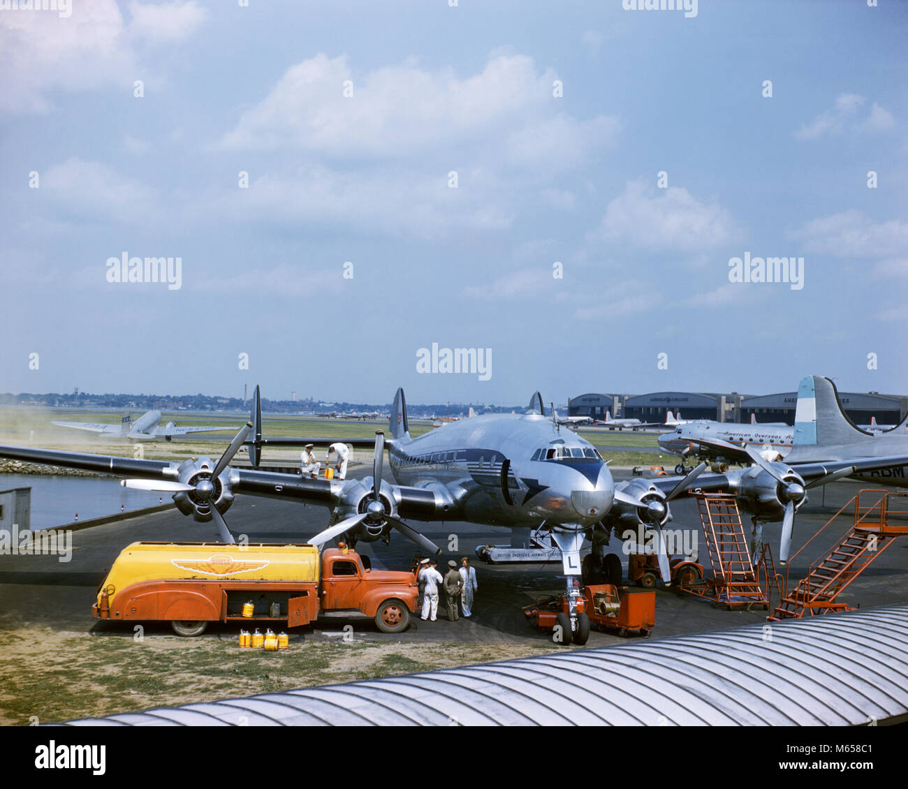 1950s CONSTELLATION PROPELLER COMMERCIAL PASSENGER AIRPLANE BEING SERVICED FOR FLIGHT TO ENGLAND LAGUARDIA AIRPORT - Stock Image