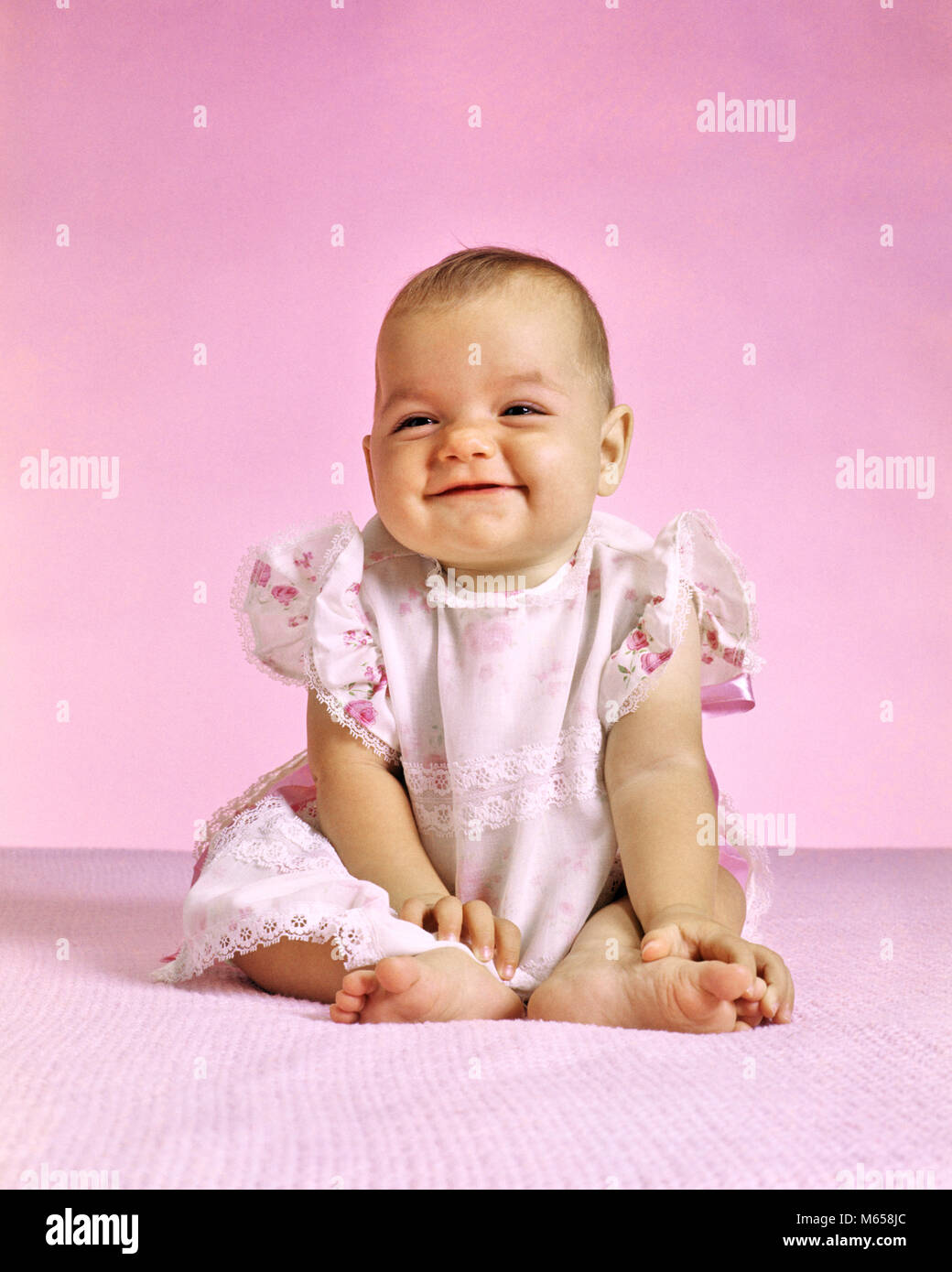 1970s BABY GIRL IN PINK SITTING SMILING - kb10543 HAR001 HARS JOYFUL 6-12 MONTHS JUVENILES BABY GIRL CAUCASIAN ETHNICITY - Stock Image