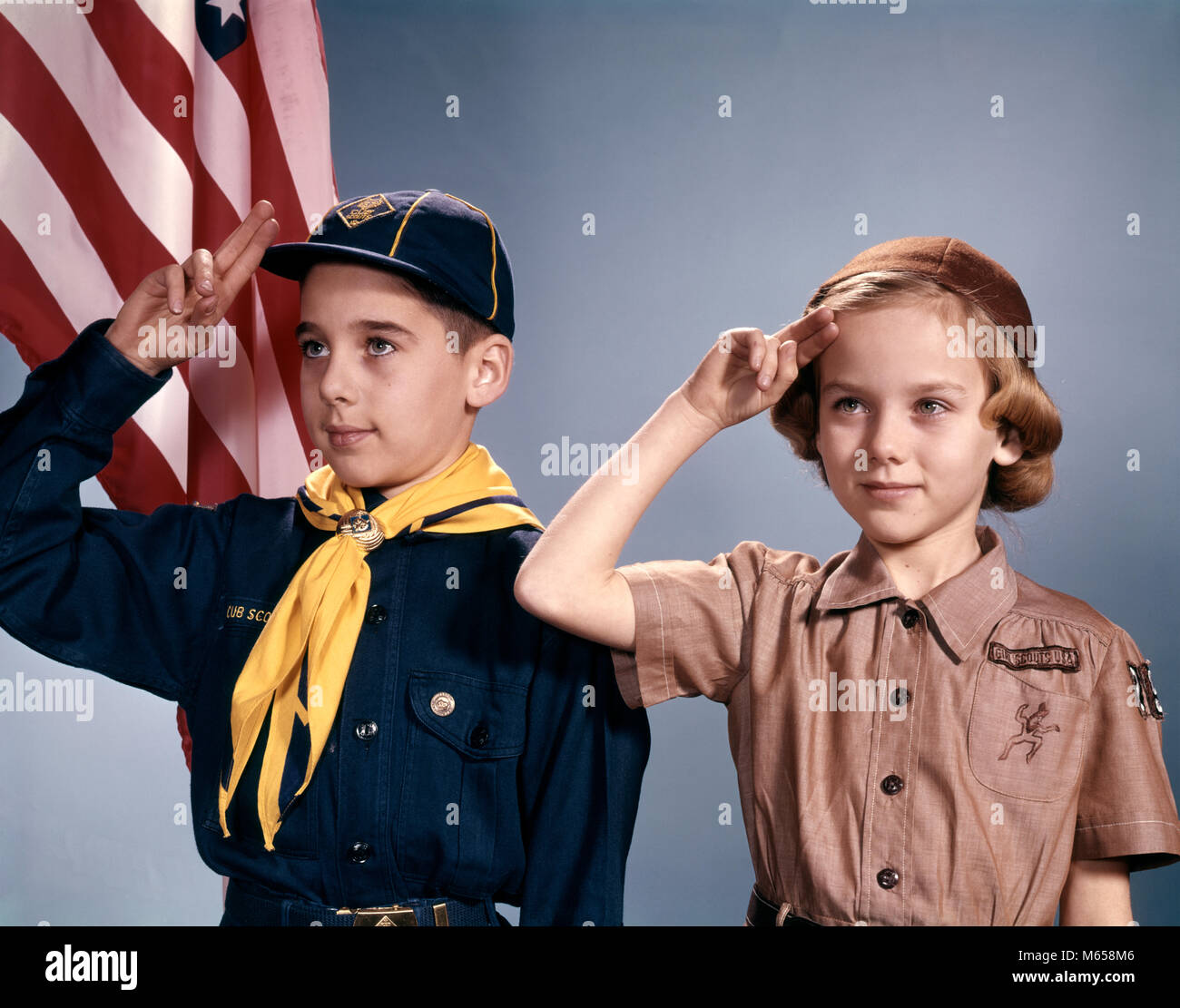 1960s BOY AND GIRL IN CUB SCOUT AND BROWNIE UNIFORMS STANDING BY AMERICAN FLAG SALUTING - kb2561 HAR001 HARS CELEBRATION - Stock Image