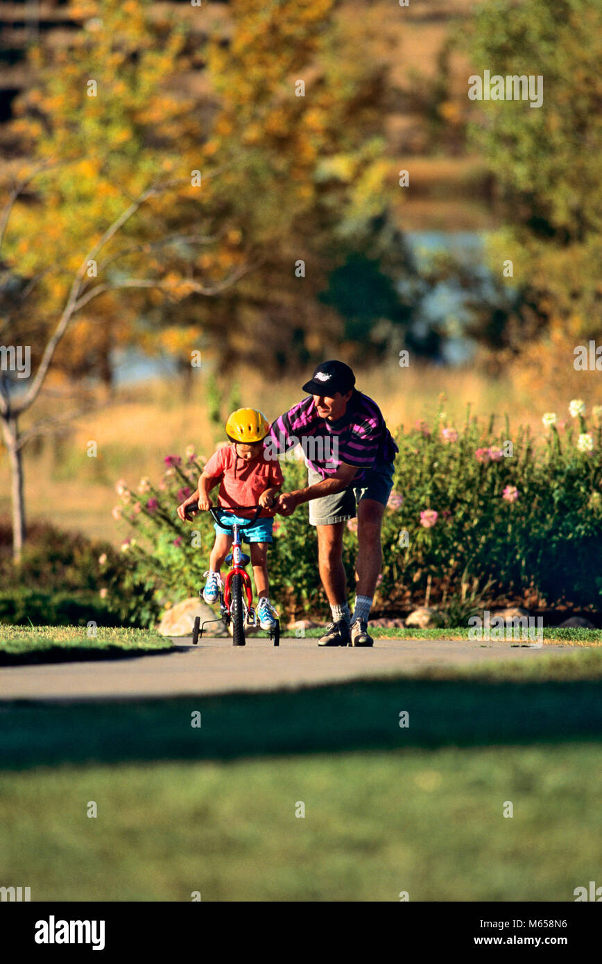 1990s FATHER TEACHING CHILD WEARING YELLOW HELMET TO RIDE BICYCLE WITH TRAINING WHEELS - kb29926 WAL004 HARS COMMUNICATION - Stock Image