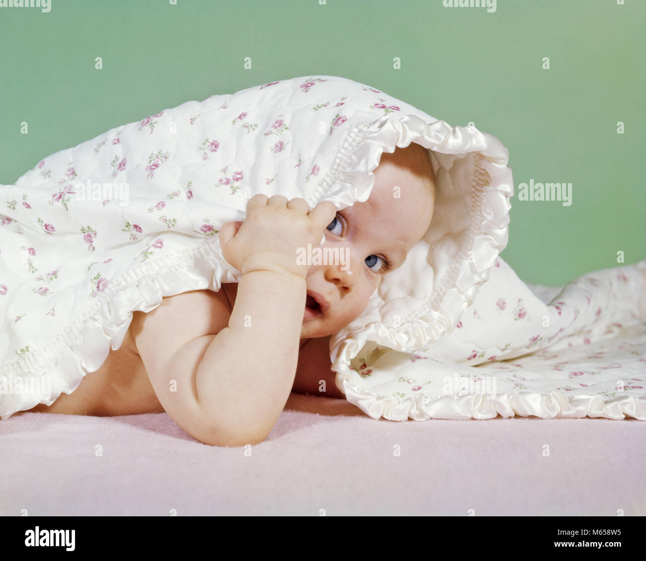 1960s BABY HIDING UNDER BLANKET LOOKING OUT LOOKING AT CAMERA - kb3371 HAR001 HARS HEAD AND SHOULDERS DISCOVERY - Stock Image