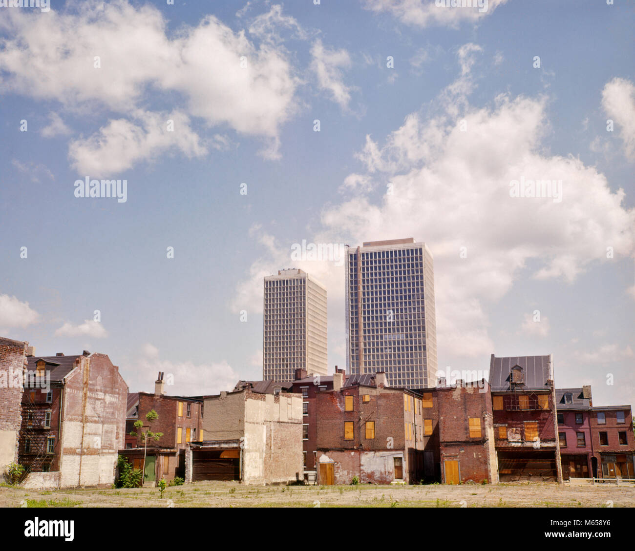 1960s URBAN RENEWAL RUN DOWN OLD HOUSES IN FOREGROUND NEW TALL APARTMENT BUILDINGS IN BACKGROUND - kb4609 HAR001 - Stock Image