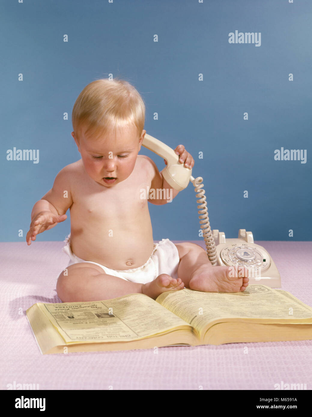 1960s BLOND BABY HOLDING TELEPHONE LOOKING AT PHONEBOOK YELLOW PAGES - kb5299 HAR001 HARS INDOORS NOSTALGIA CUSTOMER - Stock Image