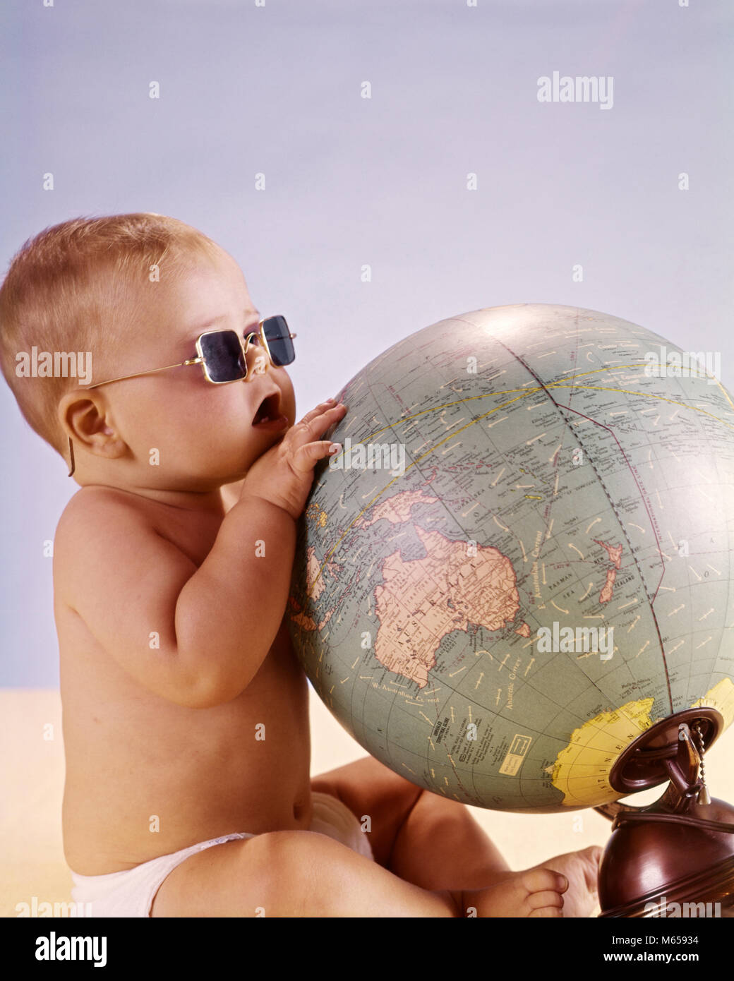 1960s BABY WEARING SUNGLASSES LOOKING LOOKING AT WORLD GLOBE MAP - kb6043 HAR001 HARS DIRECTION GROWTH CONNECTION - Stock Image