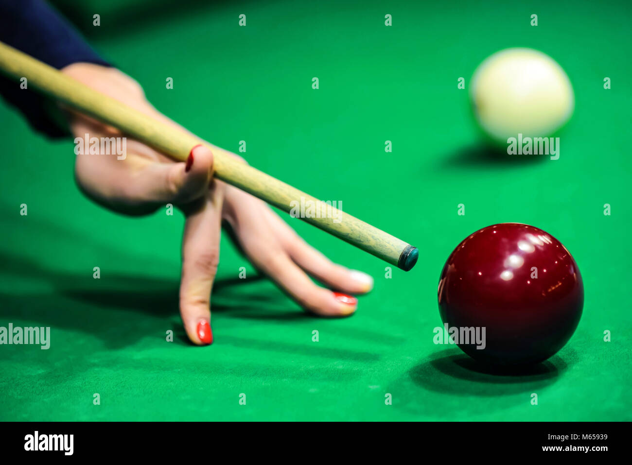 Woman's hand with cue playing pool - Stock Image